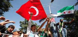 Syrian refugees wave Turkish and Syrian Independence flags during a protest against Syria's President Bashar al-Assad at Yayladagi refugee camp in Hatay province on the Turkish-Syrian border